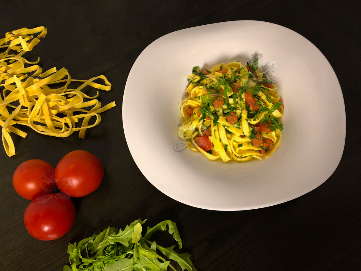 Egg tagliatelle with rocket and tomatoes in concasse